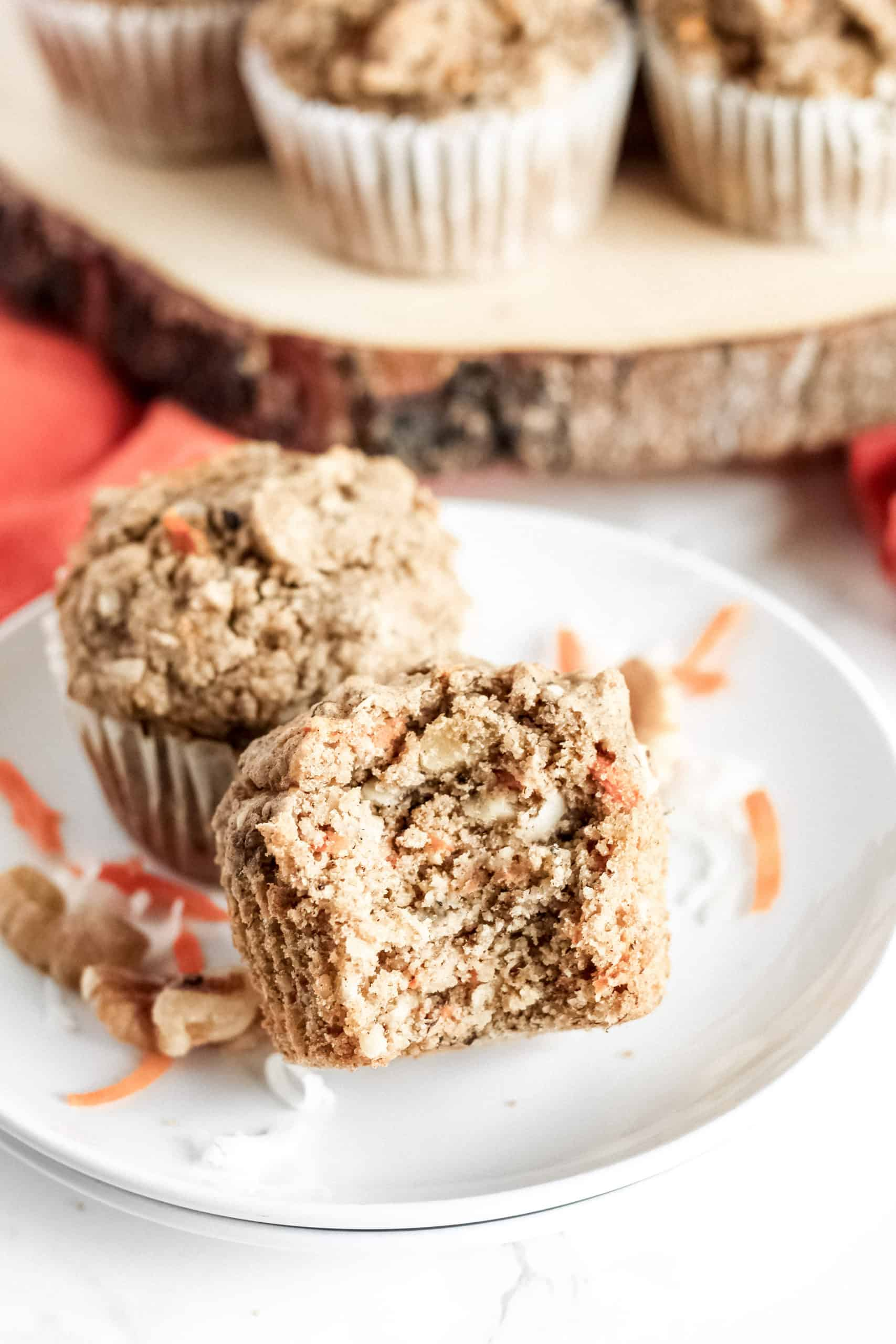 two muffins on a plate with a bite taken out
