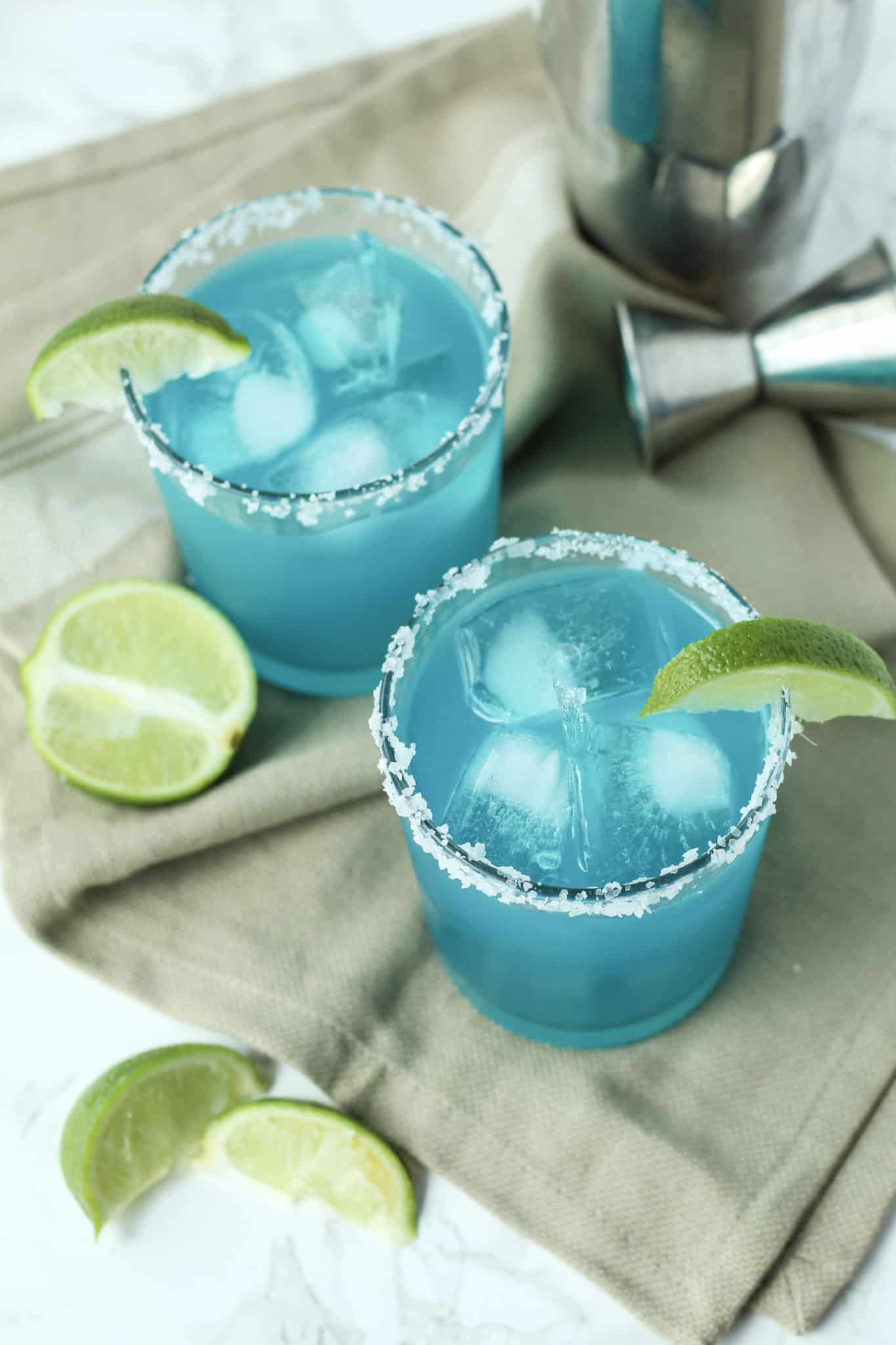 Two Blue Margaritas on a tan kitchen towel with lime slices around
