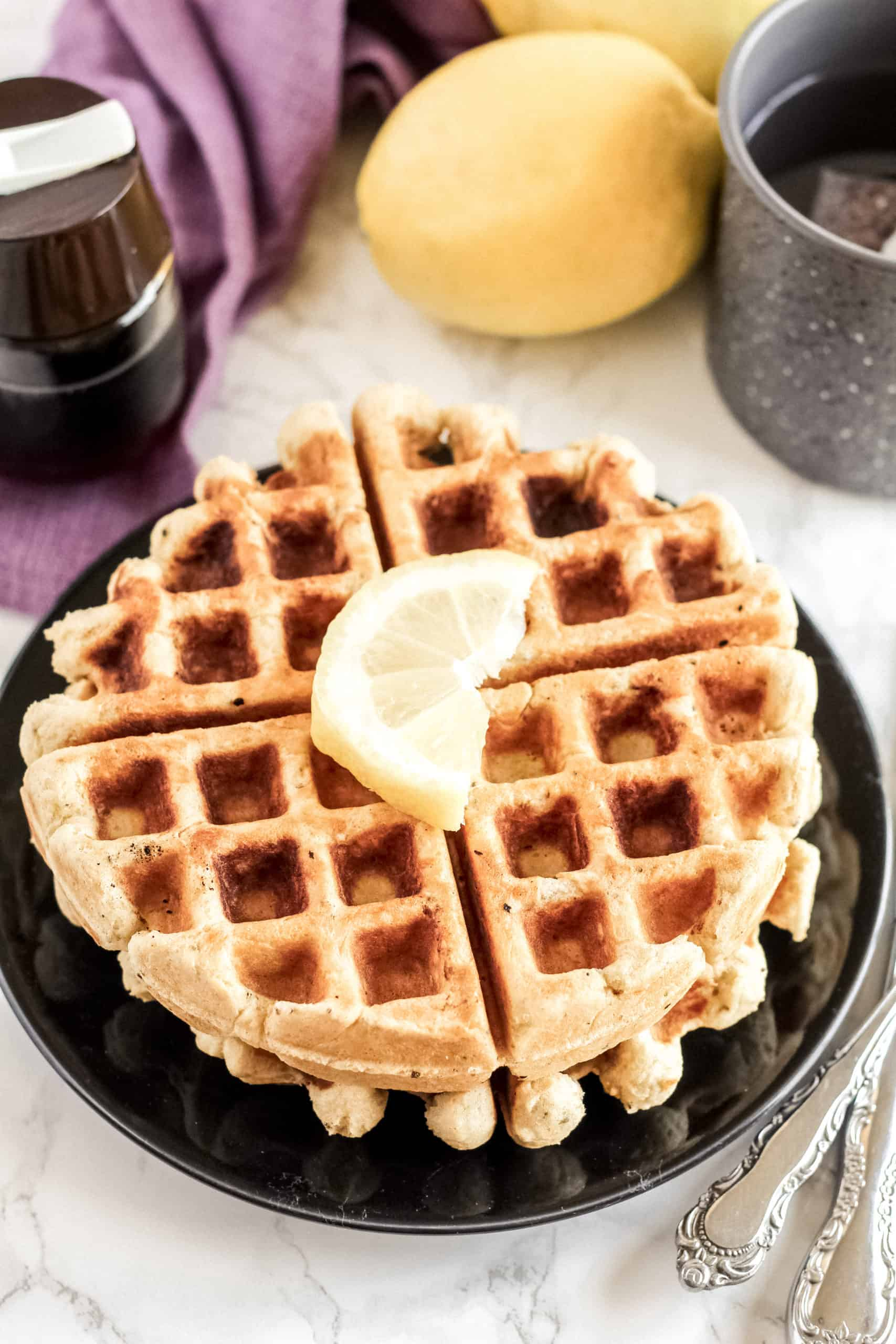 waffles on a black plate with a piece of lemon on top