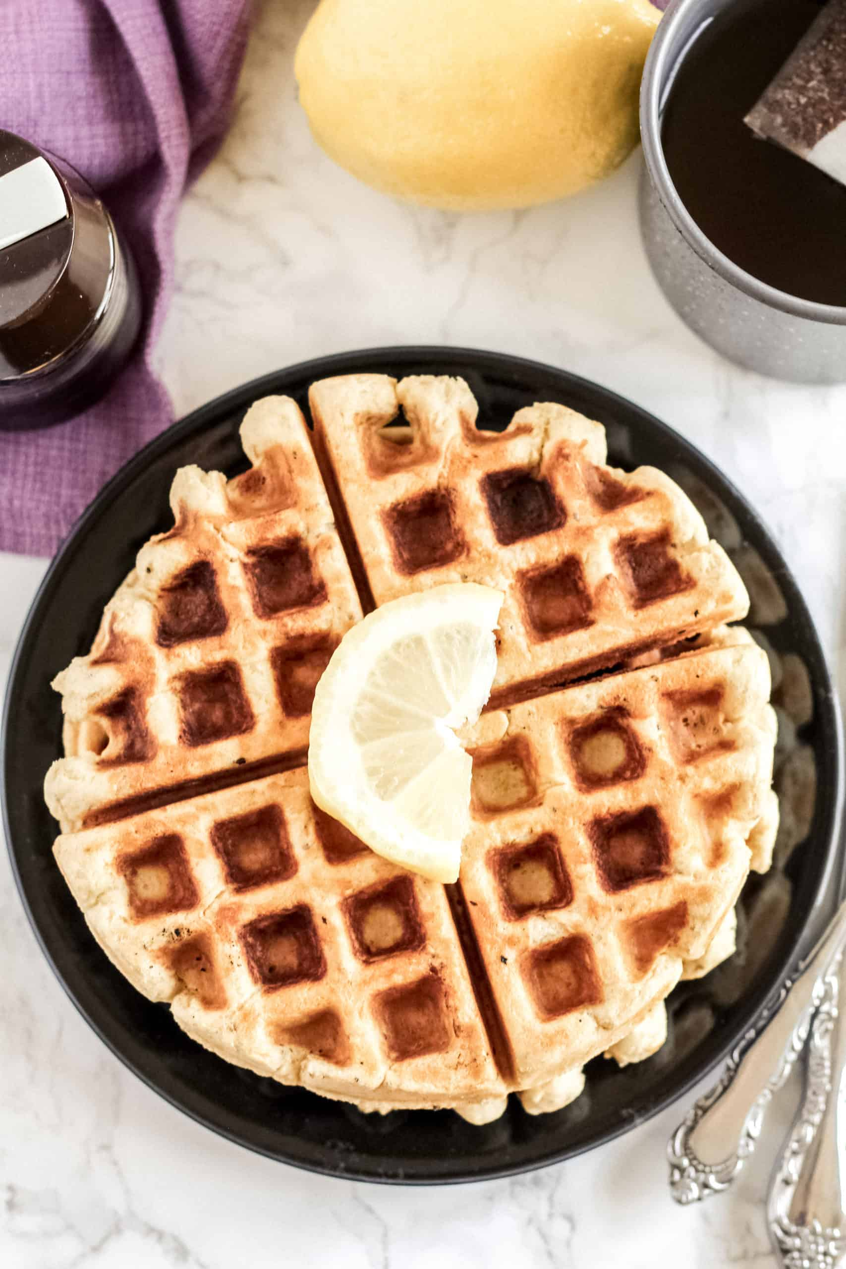 top view of waffles on a plate with a slice of lemon on top