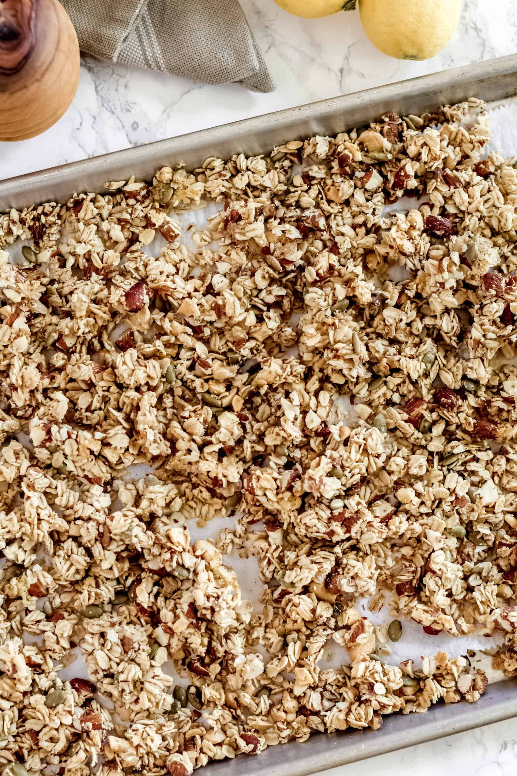 lemon honey granola on a pan with parchment paper underneath
