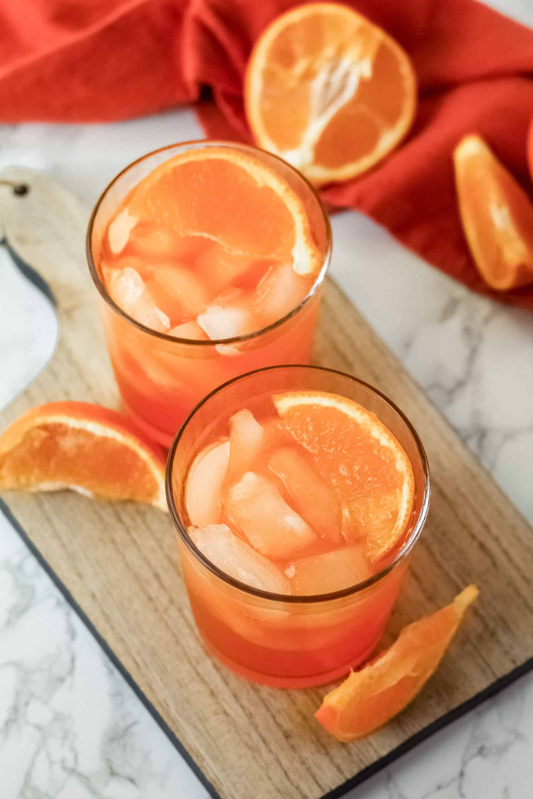 Top down view of orange slices on top of two orange thunder drinks