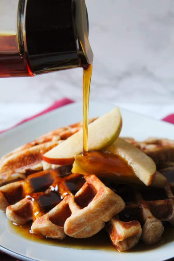 maple syrup pouring onto apples and waffles on a plate