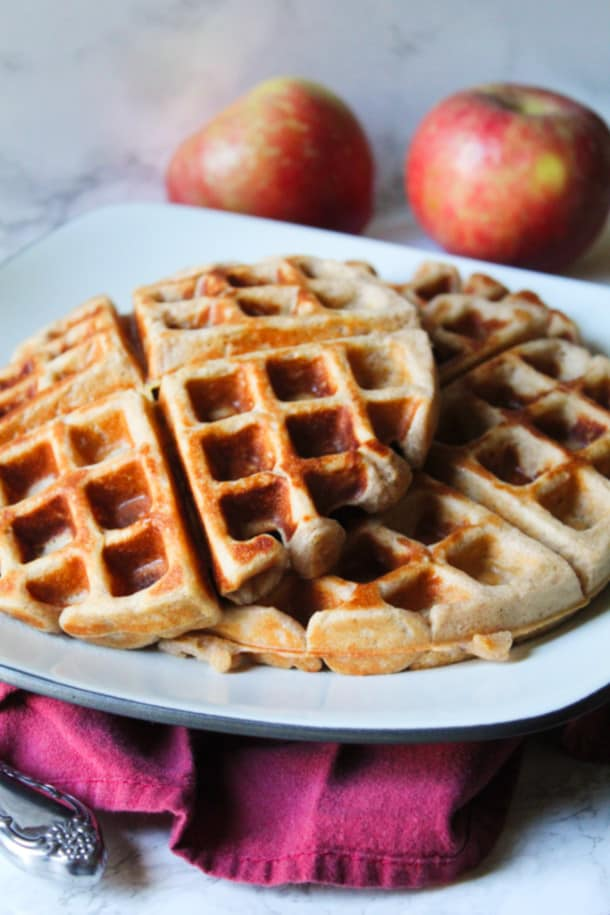two waffles on a plate with apples behind