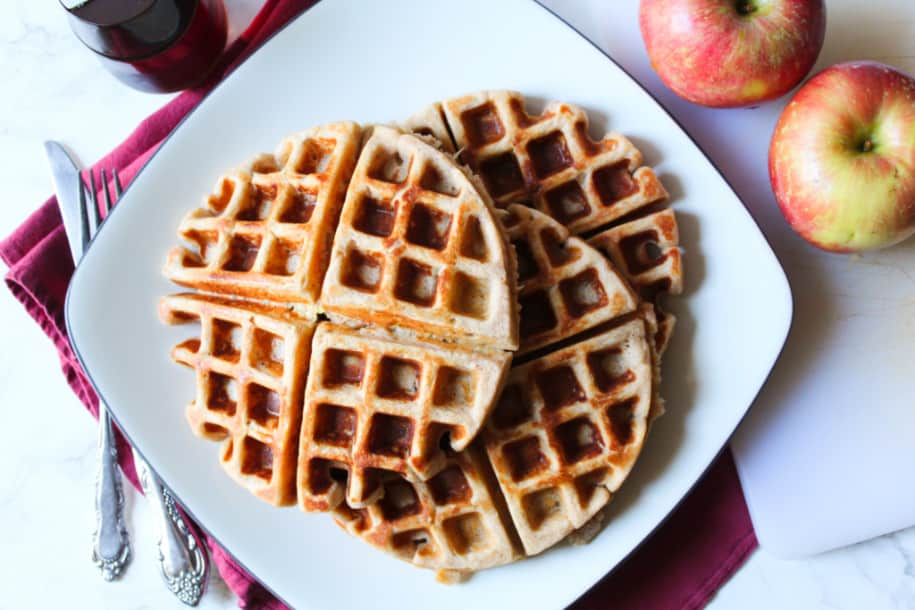 three waffles on a plate, fork, knife, apples and maple syrup