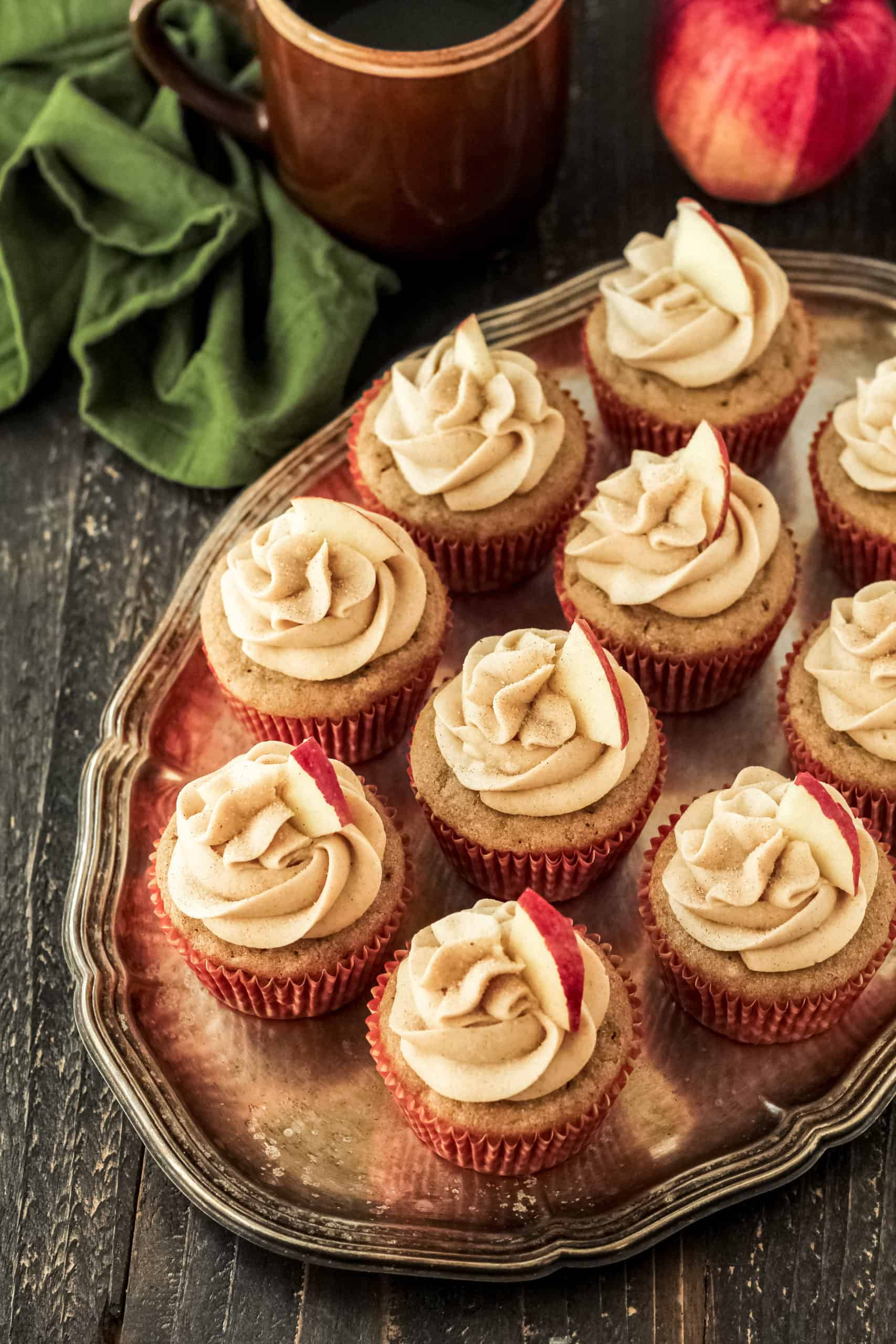 Top down view of Apple Cider Cupcakes on a tray, with apple cider and an apple in the background.