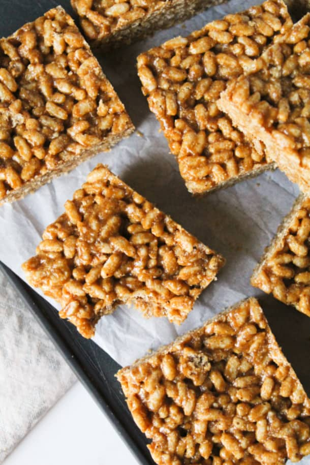 Gingerbread Rice Krispie Treats sprinkled around on parchment paper with a bite taken out of one