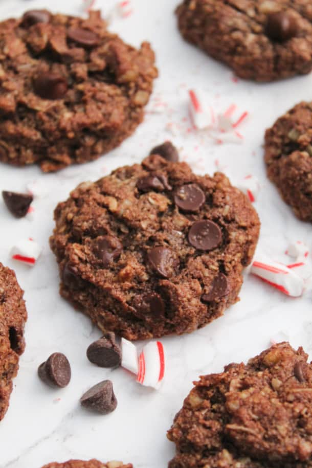 Chocolate Peppermint Breakfast Cookies on a counter with chocolate chips and candy cane bits sprinkled around
