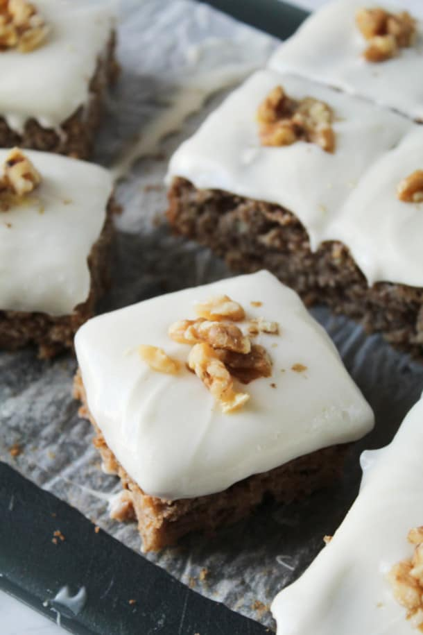 Spice Cake on a cutting board with frosting and nuts on top