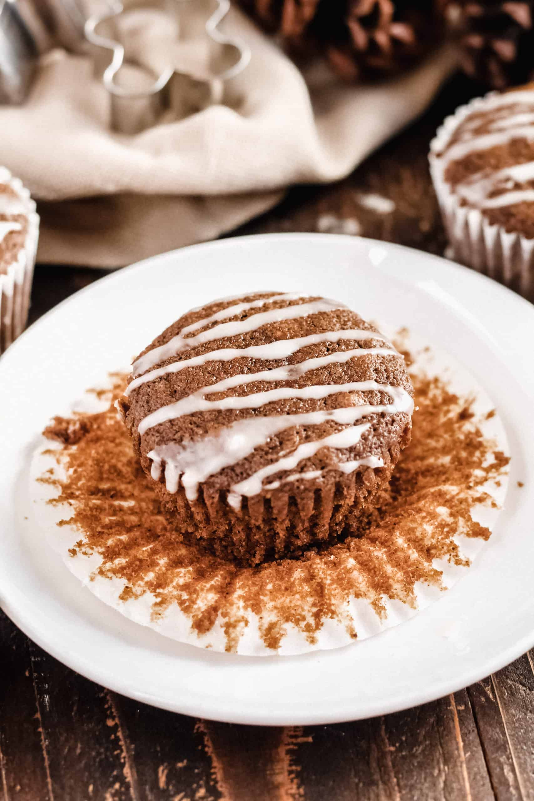 one gingerbread muffin unwrapped out of a cupcake liner on a plate