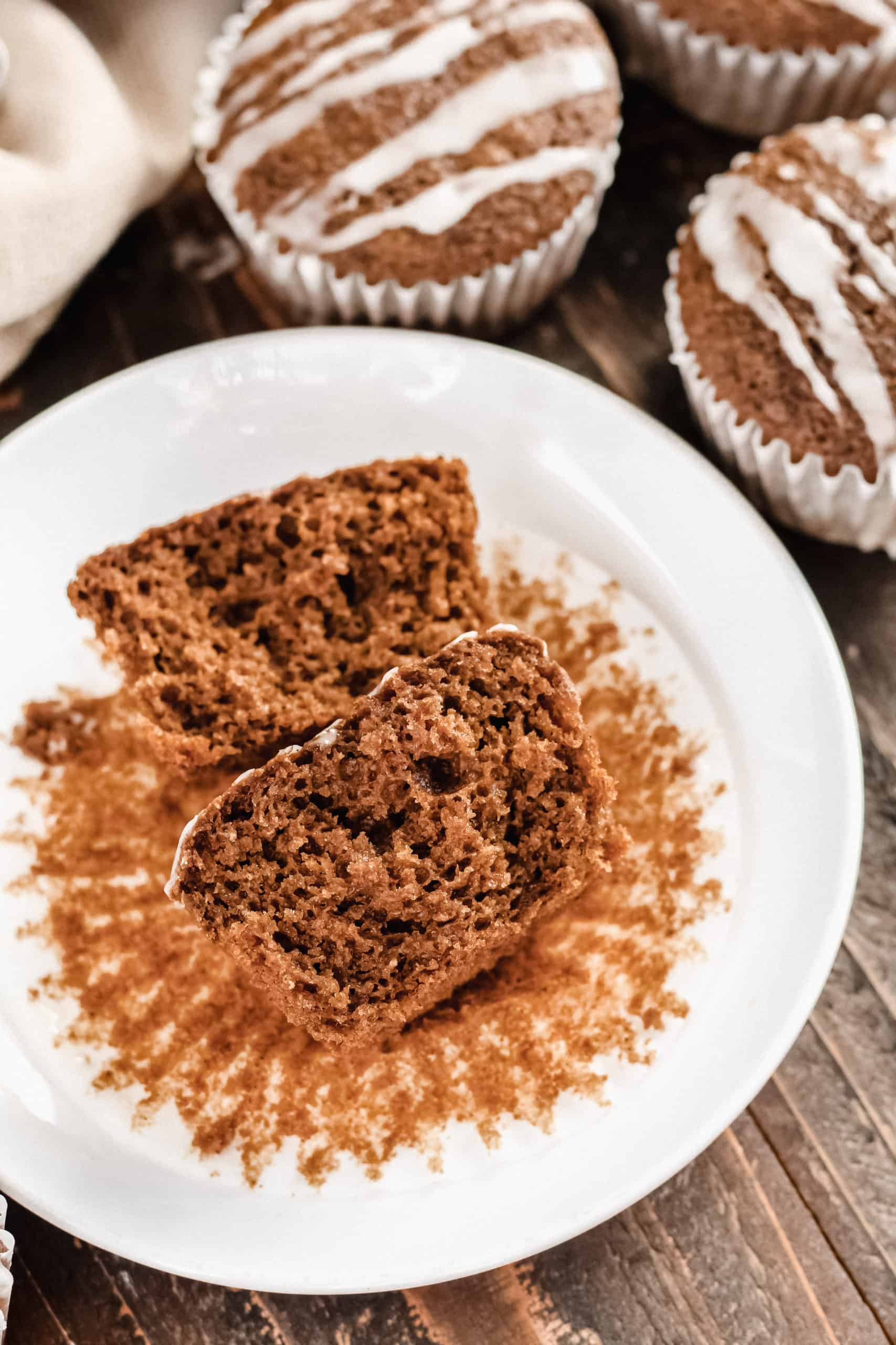 One gingerbread muffin cut in half to see the inside, on a plate