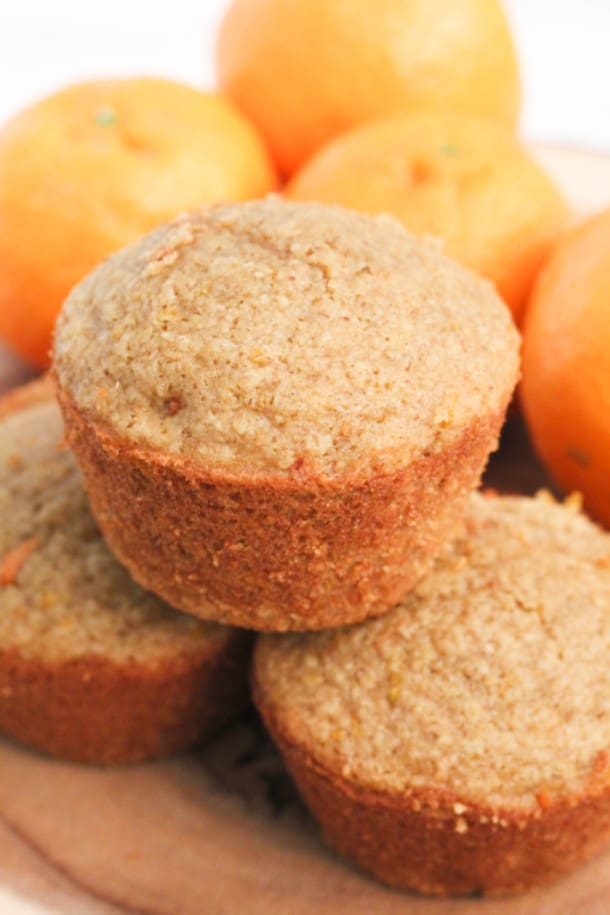 Orange Carrot Oat Muffins stacked on top of each other with oranges behind