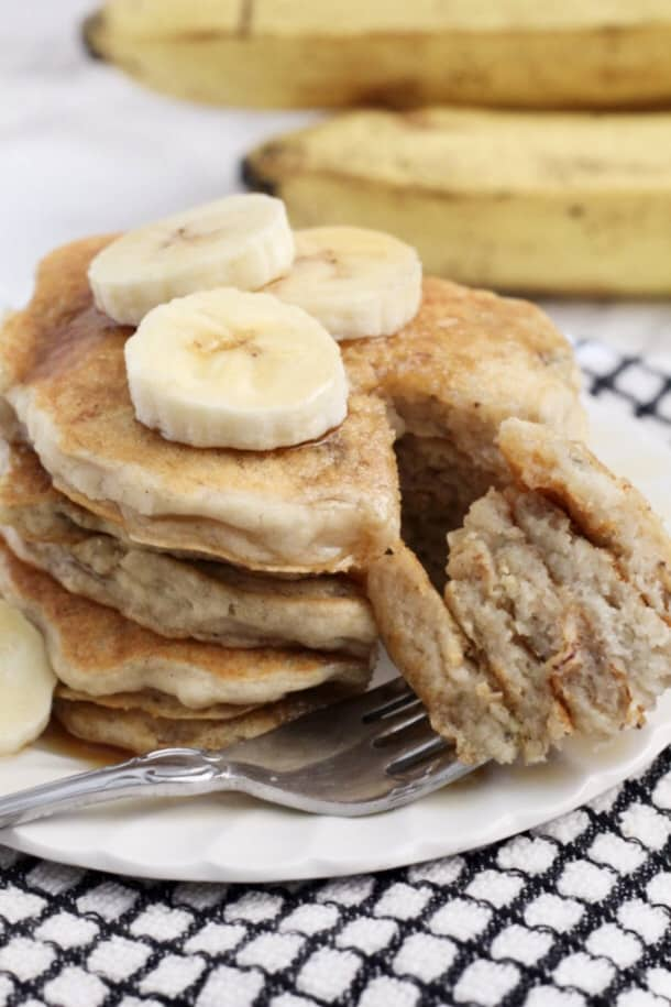 Banana Pancakes on a plate with a fork full of pancake