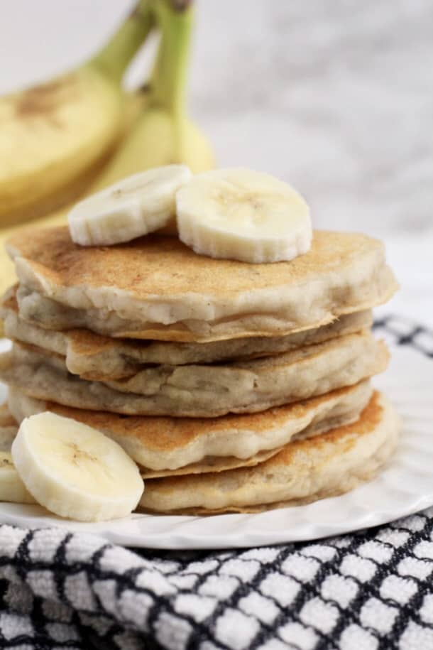 Banana Pancakes stacked on a plate with slices of banana on top and beside