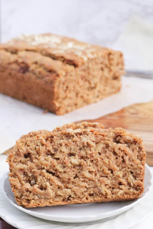 two slices of Cinnamon Applesauce Oat Bread on a plate, with the loaf behind