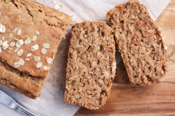 a loaf of Cinnamon Applesauce Oat Bread on a wood tray with parchment paper, with two slices cut out of the front