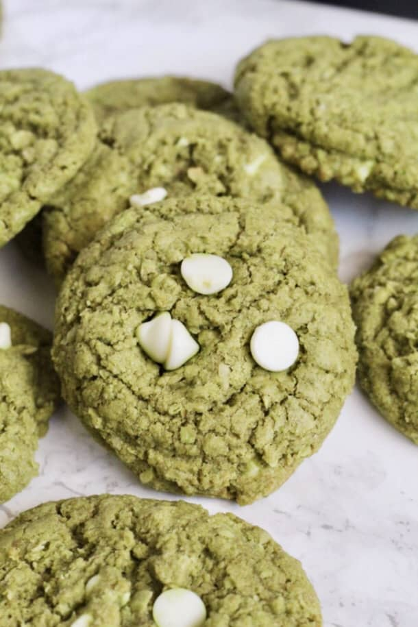 Matcha Oatmeal White Chocolate Chip Cookies laid out on a counter