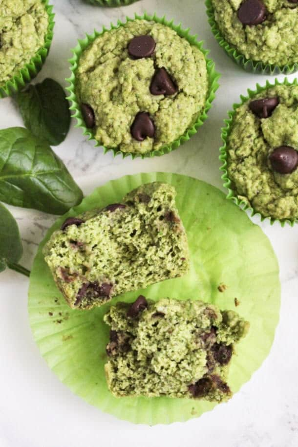 Mint Chocolate Chip Oat Muffins with one cut open in half, and a couple pieces of spinach around