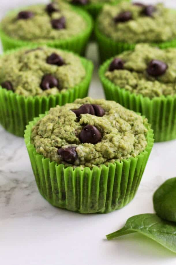 Mint Chocolate Chip Oat Muffins on a counter with a couple pieces of spinach next to them