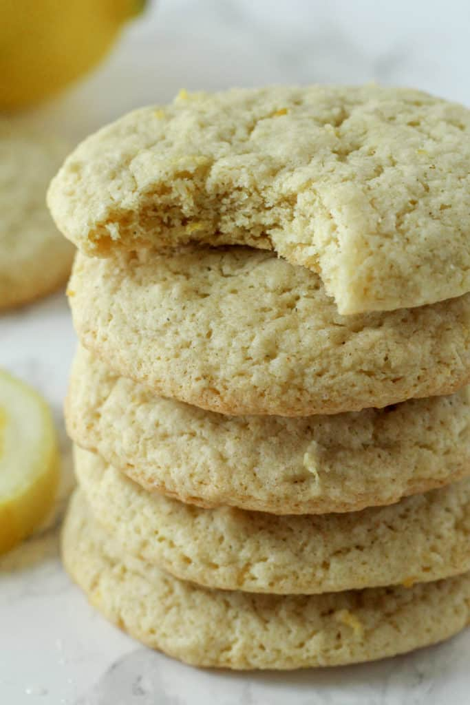 close up view of a stack of Lemon Cookies with a bite taken out of the top one