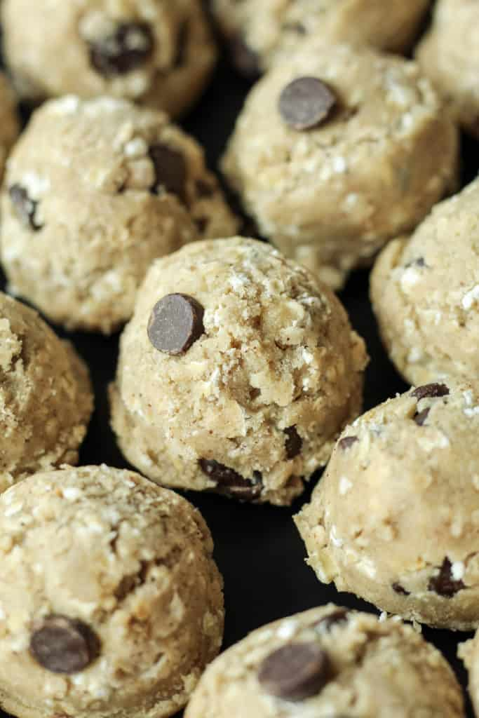cookie dough balls of Oatmeal Chocolate Chip Cookies on a black plate