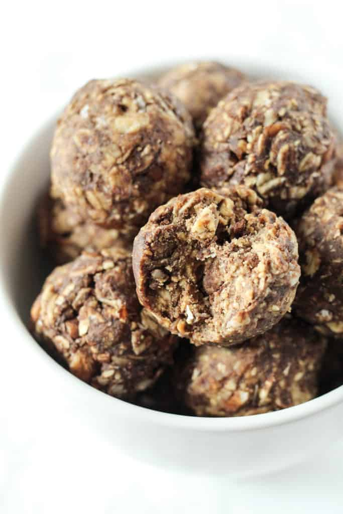 a bowl of Chocolate Peanut Butter Snack Ball with a bite taken out of one