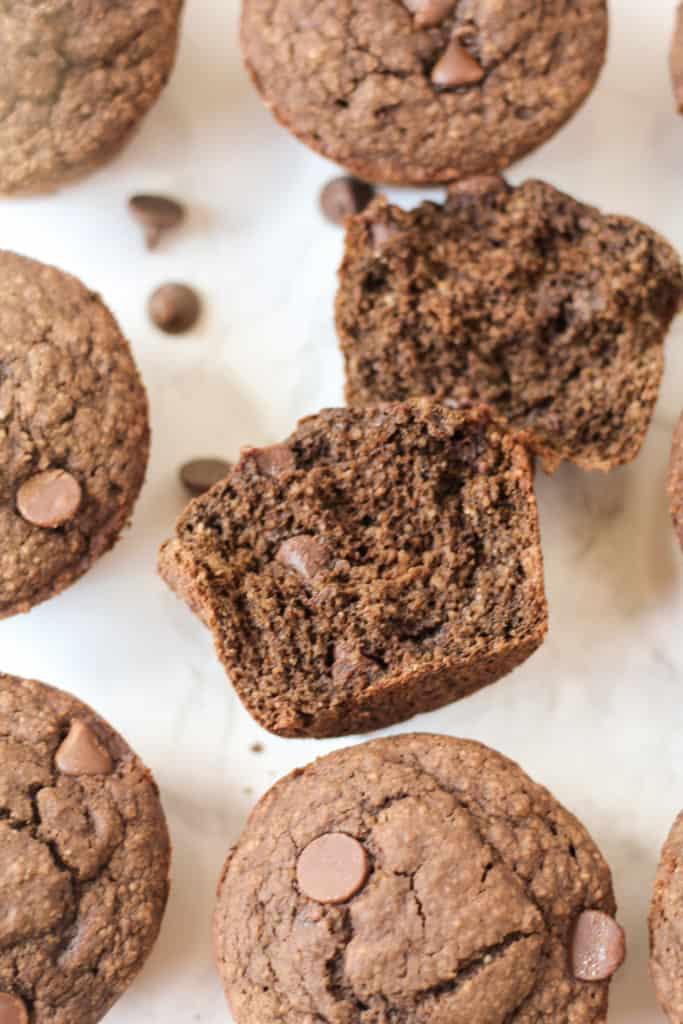 Double Chocolate Oat Muffins scattered around on parchment paper, with one cut open to see inside