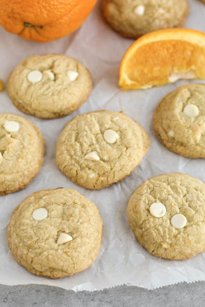 Gluten-free Orange Cookies on a parchment paper scattered around