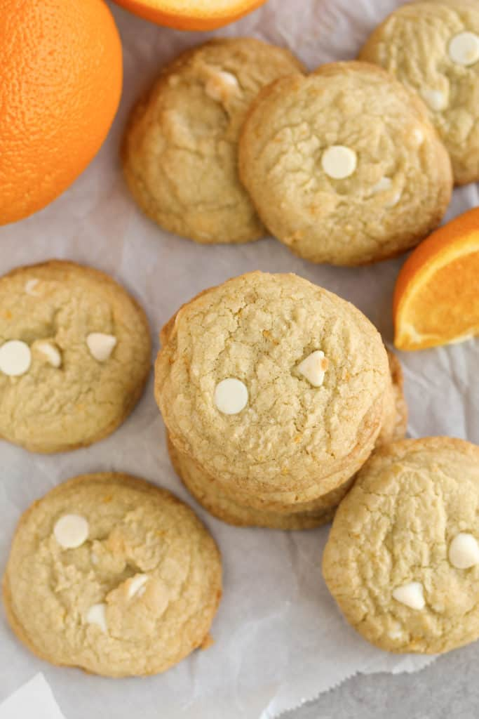 A stack of Orange Cookies surrounded by other cookies and orange slices
