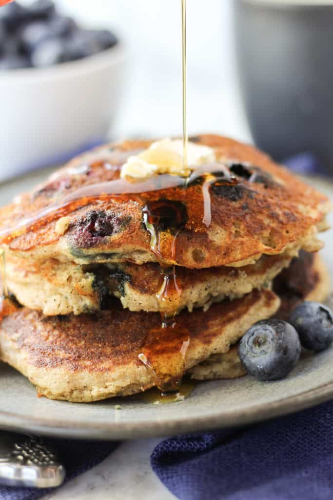 Blueberry Pancakes in a stack of three on a plate with maple syrup drizzling down them