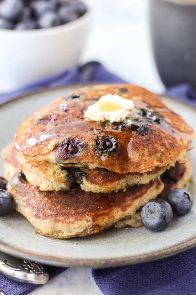 a blue plate with three Blueberry Pancakes stacked on top with butter
