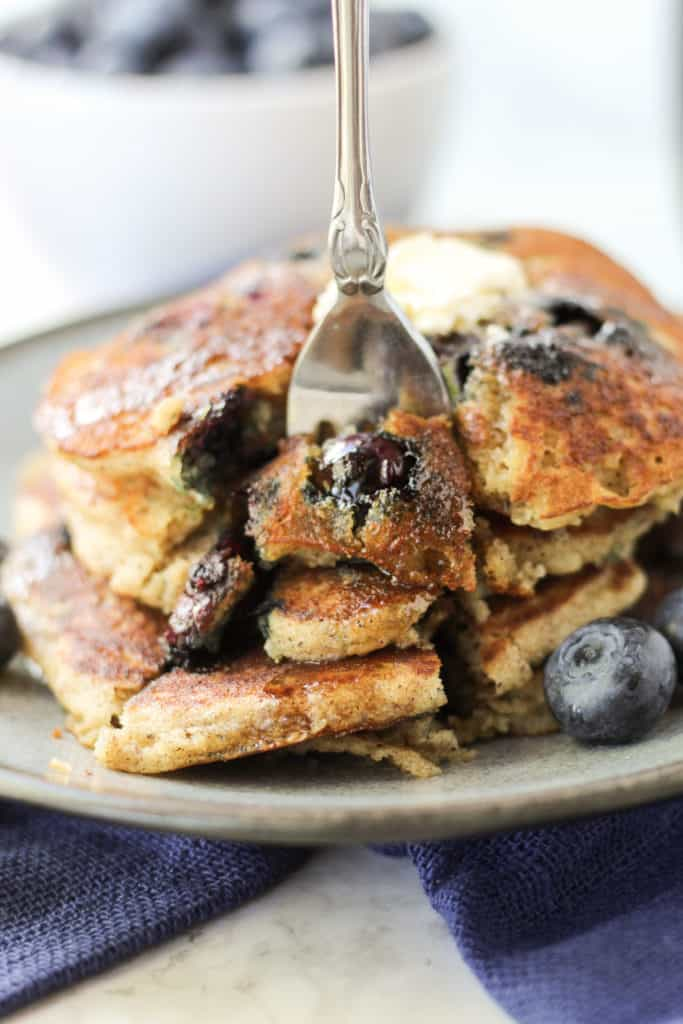 a blue plate with a stack of three Blueberry Pancakes with a fork stuck in it