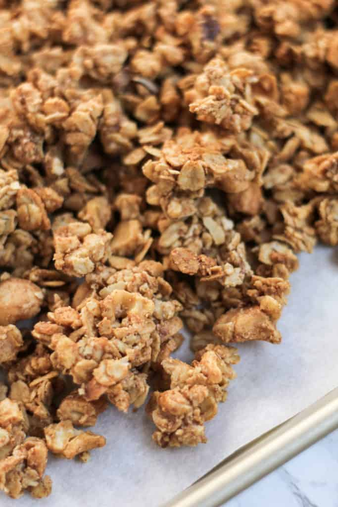 close up view of clusters of Cinnamon Cashew Granola on a pan