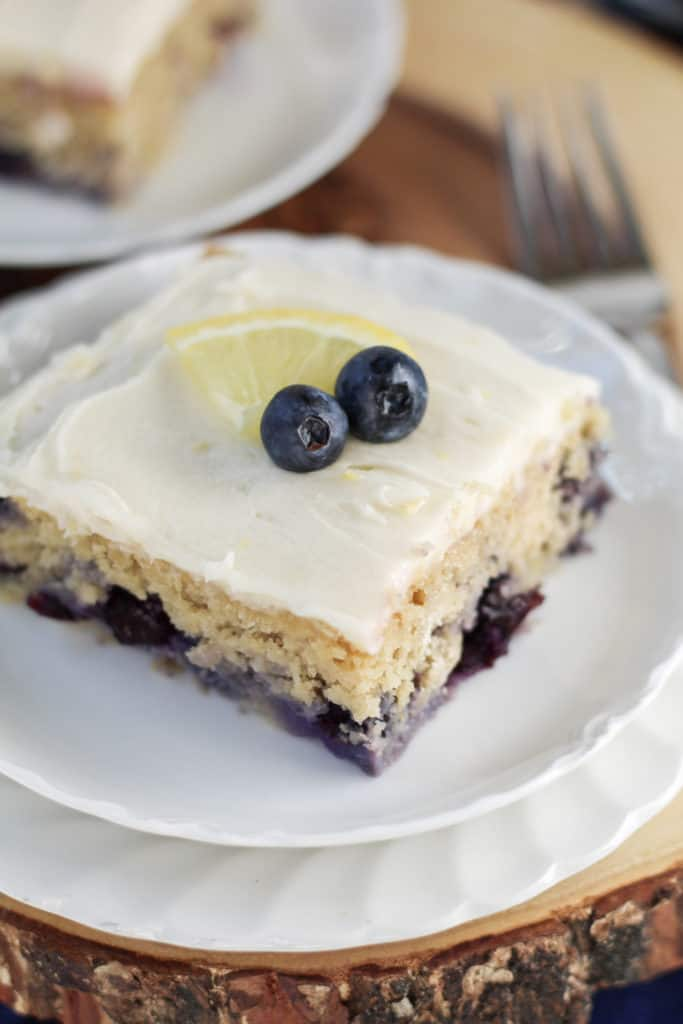 One piece of Lemon Blueberry Oat Cake on two plates, with a lemon slice and blueberries on top