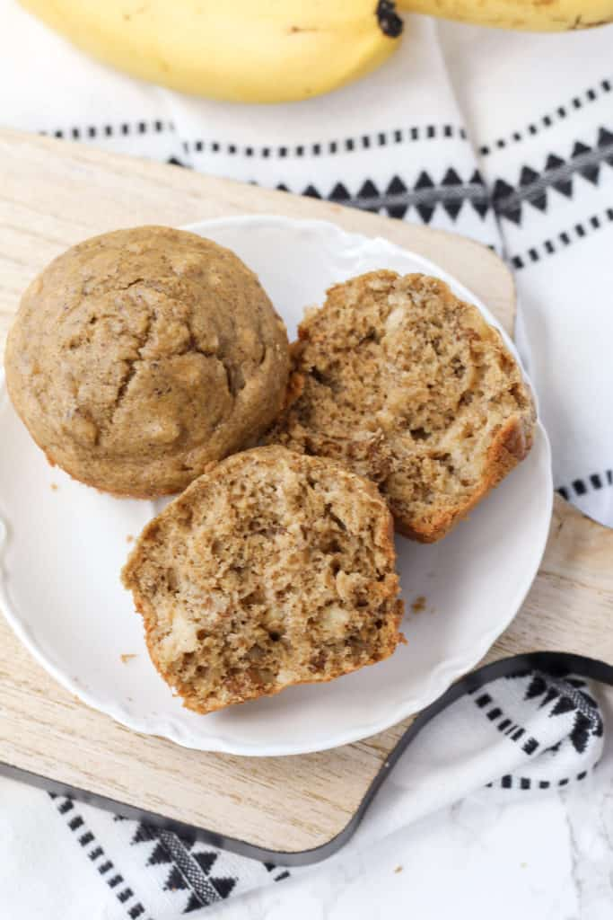 a plate with two banana nut oat muffins, with one cut open to see the inside