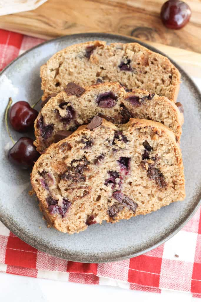 A blue plate with three slices of Dark Chocolate Chunk Cherry Bread and a couple cherries
