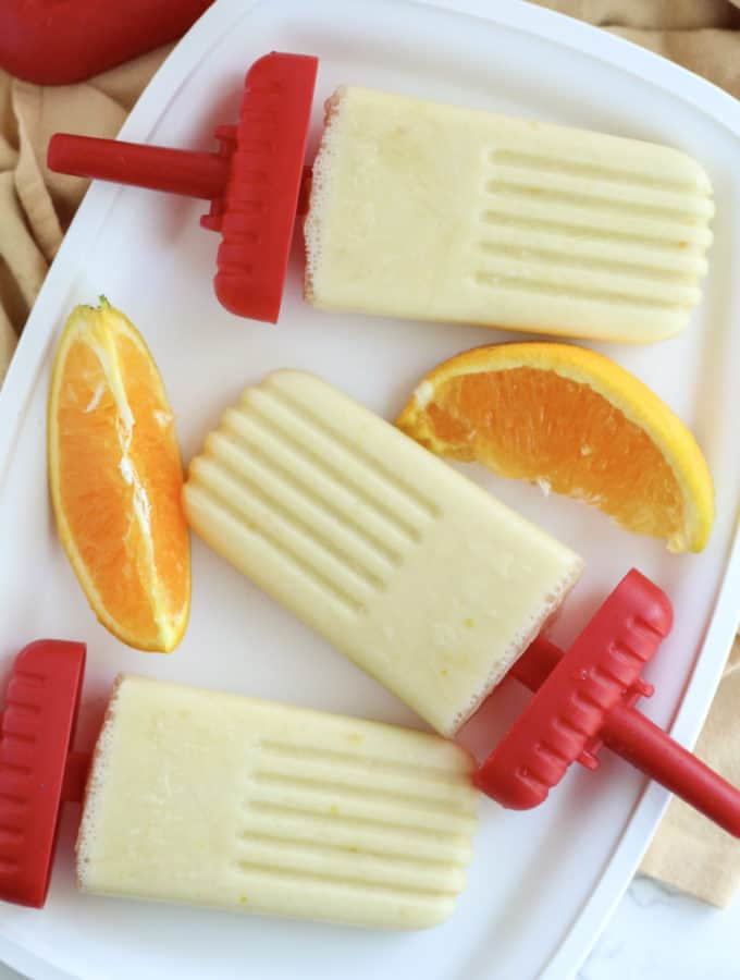A plate with orange popsicles