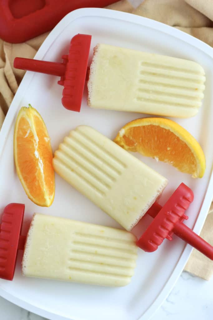 three Orange Creamsicle Popsicles on a tray with slices of orange