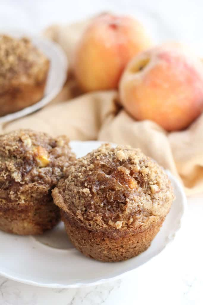 A plate with two Peach Pecan Oat Muffins, and peaches behind
