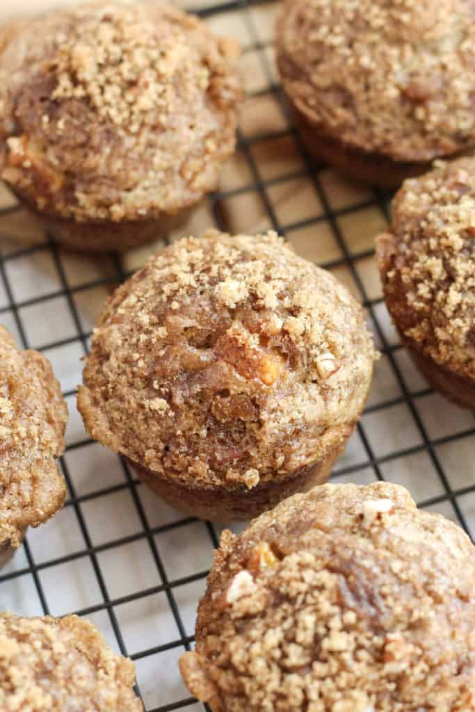 A cooling rack with one Peach Pecan Oat Muffin up close