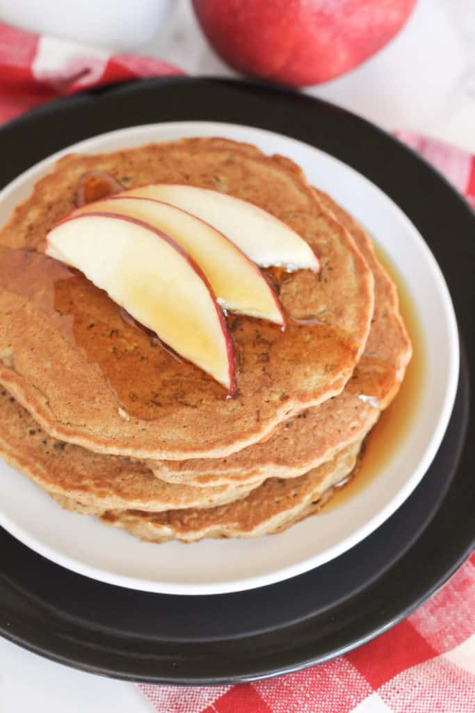 A stack of Apple Cinnamon Oat Pancakes on two plates with apple slices and maple syrup on top