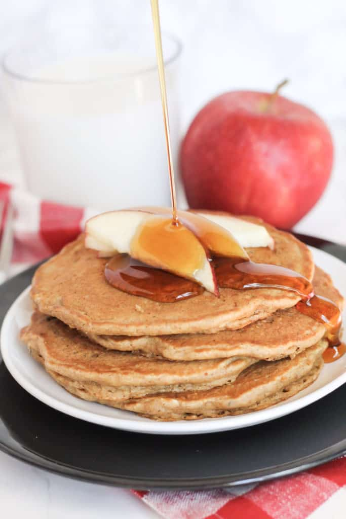 A side view of four Apple Cinnamon Oat Pancakes on a plate with apple slices and maple syrup pouring on top