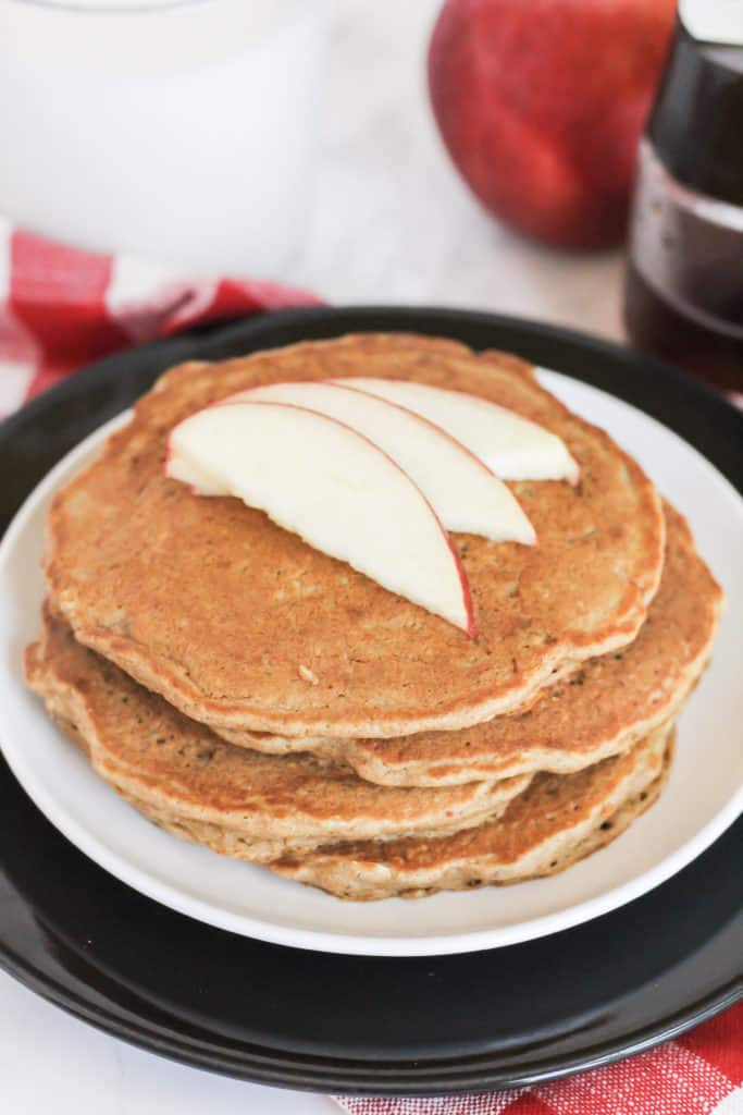 A stack of three Apple Cinnamon Oat Pancakes on two plates with slices of apple on top