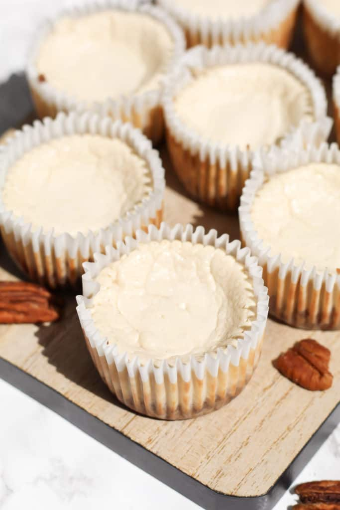 A wood tray filled with Skinny Mini Maple Pecan Cheesecakes