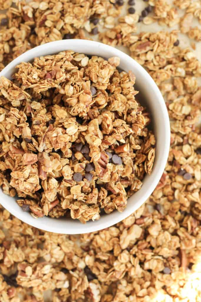 Pumpkin Chocolate Chip Granola in a bowl and granola surrounding the bowl