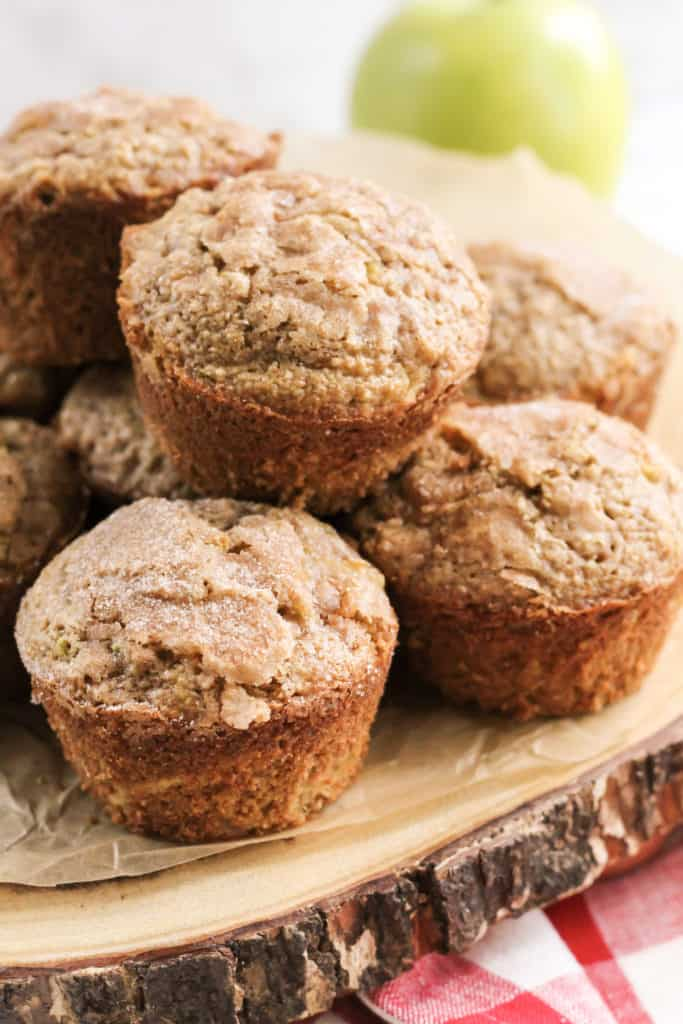 Apple Cinnamon Oat Muffins stacked on each other on a wood tray