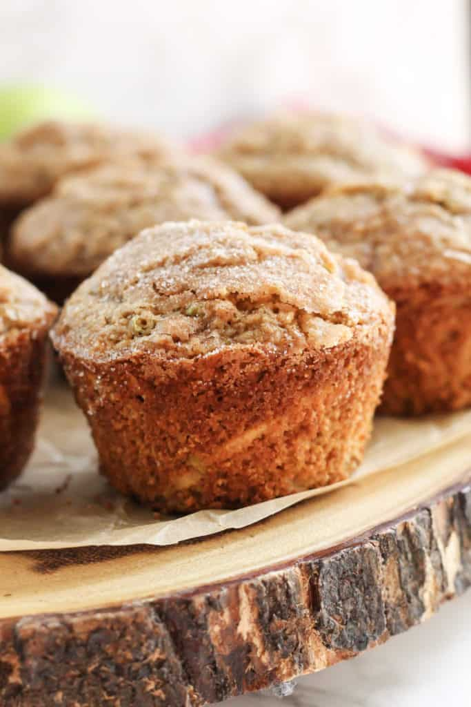 A close up of one Apple Cinnamon Oat Muffins on a wood tray