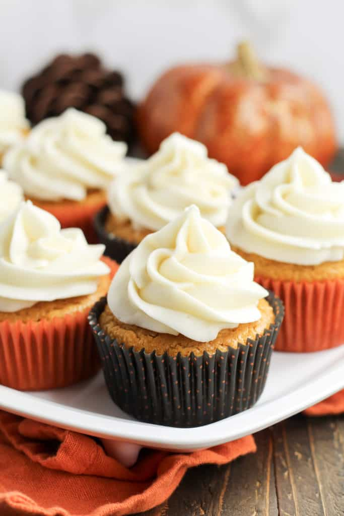 Pumpkin Cupcakes on a tray with an orange dish cloth