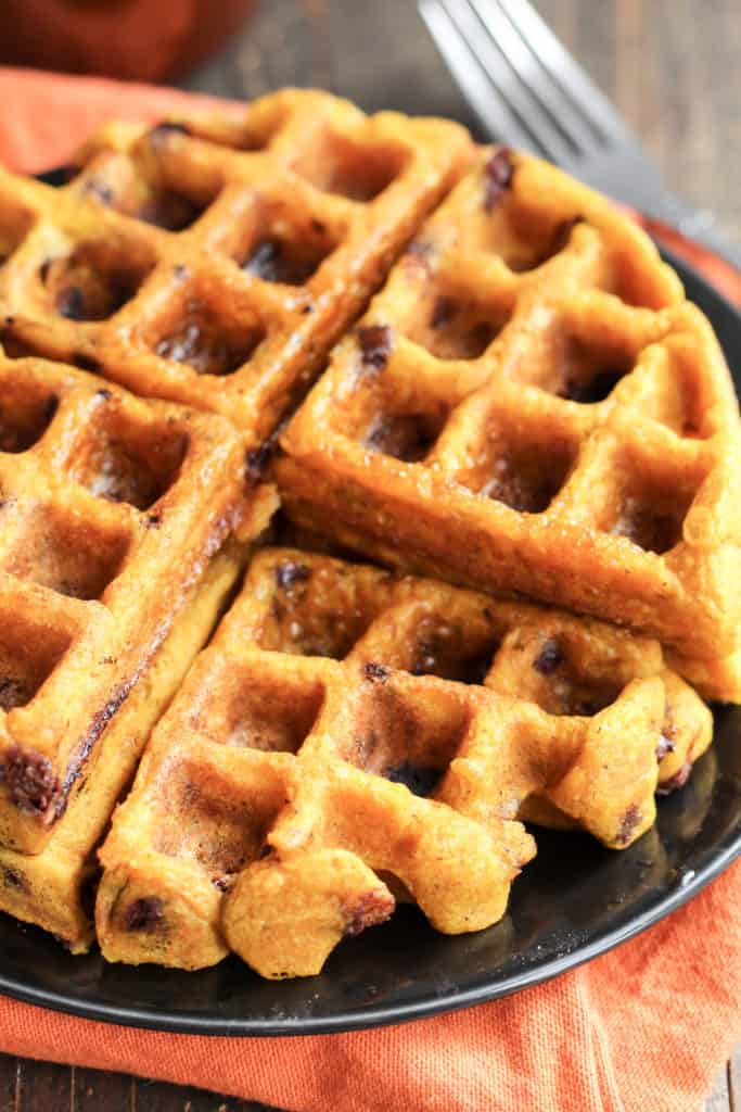 Pumpkin Chocolate Chip Waffles on a black plate, with one piece removed to see the inside of the waffles