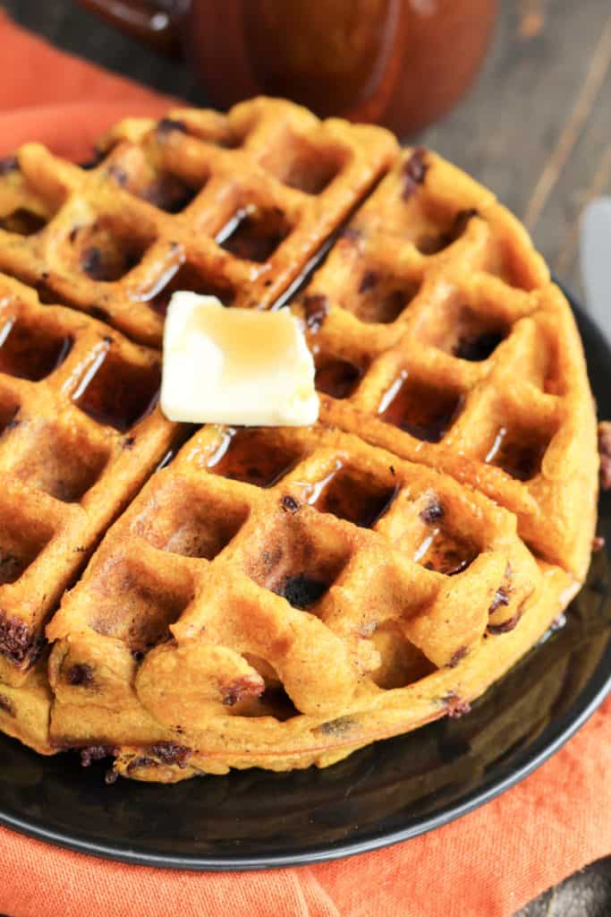 A black plate with two Pumpkin Chocolate Chip Waffles stacked with butter and maple syrup